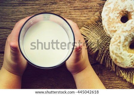A glass of milk in the hands of a child. - stock photo