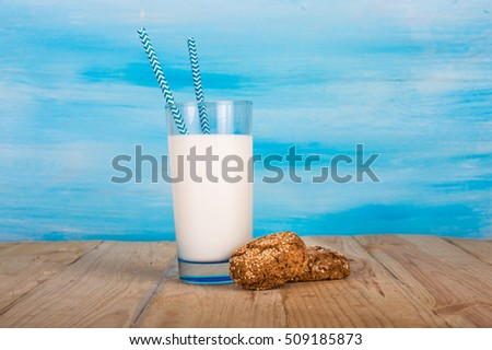 A glass of milk with straws and cookies. On a blue background.
