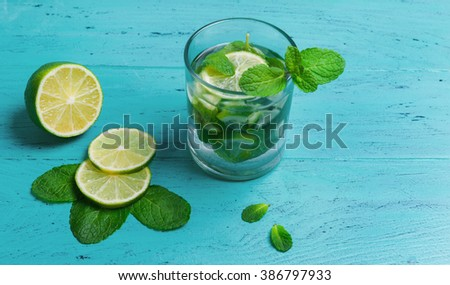 A glass of mojito cocktail with lime and mint on green wooden background, empty clean place for your text