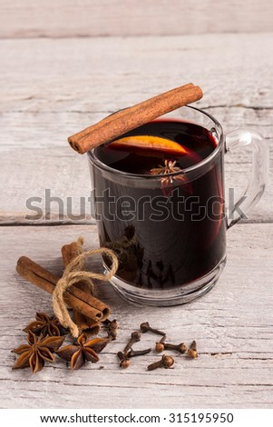 a glass of mulled wine with spices and orange - stock photo