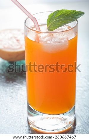 A glass of orange flavored carbonated drink
