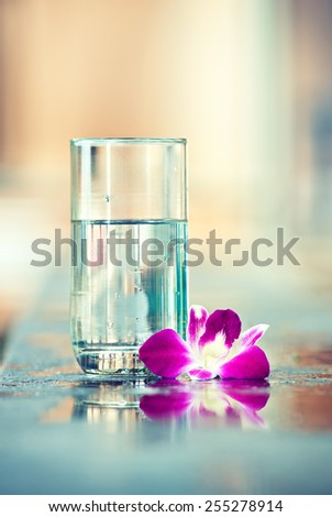 A glass of pure water with flower orchids near - stock photo