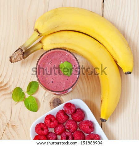 A glass of raspberry smoothie with fresh raspberries, mint leaves and banana - stock photo