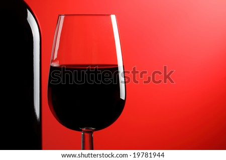 A glass of red wine and bottle on a red background.