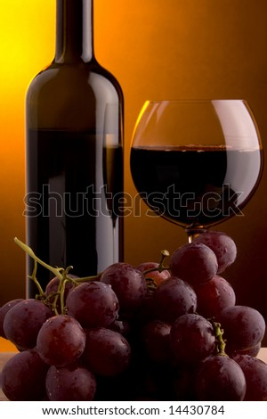 a glass of red wine and grape and a bottle