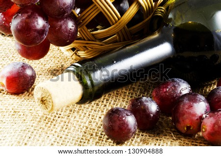 A glass of red wine and grapes in a basket on a jute texture - stock photo