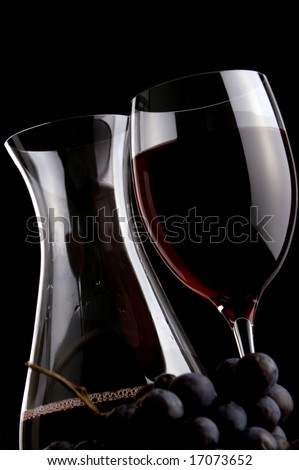 a glass of red wine jug and grape