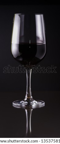 a glass of red wine on black background with reflection - stock photo