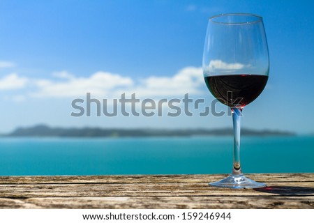 A Glass of Red Wine Standing on Old Table at the Beach on the Pacific Coast, Auckland, New Zealand