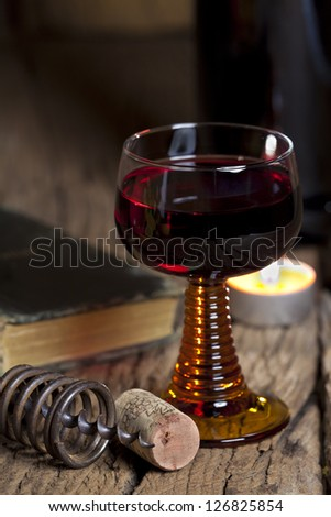A glass of red wine stands on an old rustic table with candle