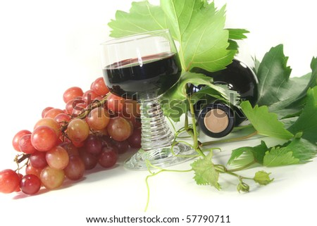 a glass of red wine with bottle, grapes and leaves