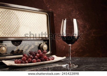 A glass of red wine with music from the radio - stock photo
