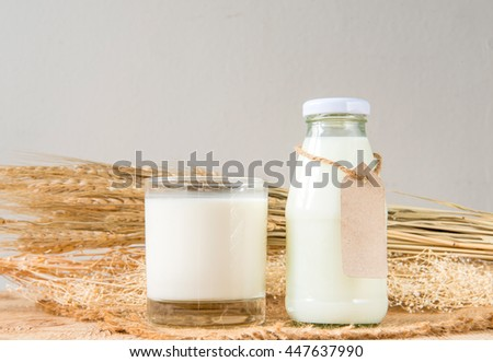 A glass of rustic milk and bottle glass of rustic milk and ear of rice dry on a wood table, tasty, nutritious and healthy dairy products