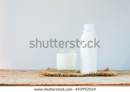 A glass of rustic milk and bottle of rustic milk on a wood table on white background, tasty, nutritious and healthy dairy products - stock photo