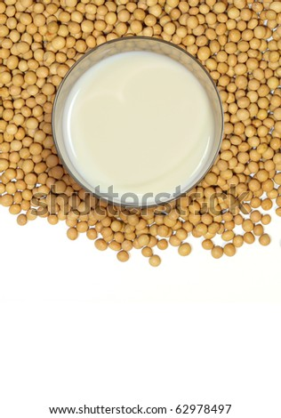 A glass of soy milk over a pile of soybean