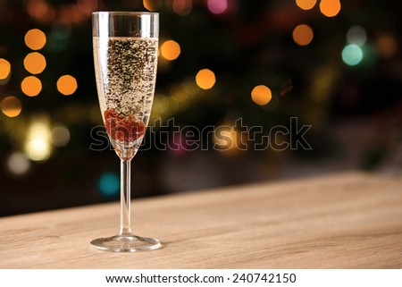 A glass of sparkling wine with jam on the table - stock photo