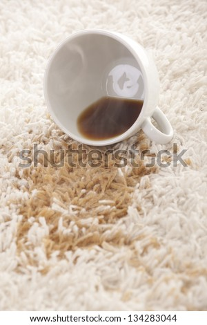 A glass of spilled coffee  on brand new carpet is sure to leave a stain. - stock photo