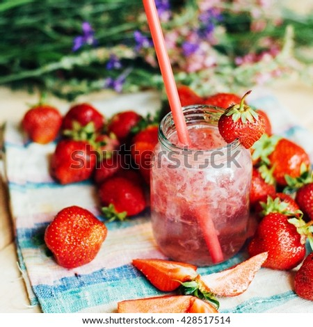 A glass of strawberry smoothie on a wooden background. Strawberry smoothie. Closeup of strawberry fruit smoothies with strawberry pieces in glass with straw. Strawberry smoothie on rustic wood - stock photo