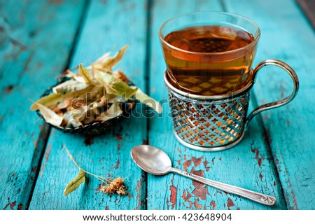 A glass of tea with a linden on blue vintage background  - stock photo