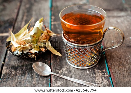 A glass of tea with a linden on vintage background - stock photo
