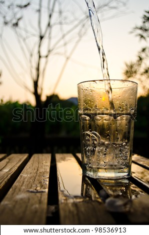 a glass of water in sunset background