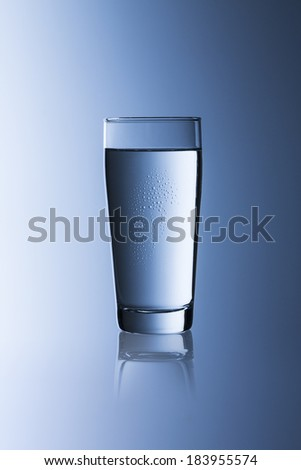 A glass of water with drinking water on blue gradient willi cup background with reflection - stock photo