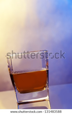 a glass of whiskey against color background - stock photo