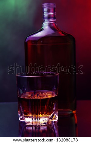 a glass of whiskey and bottle against color background