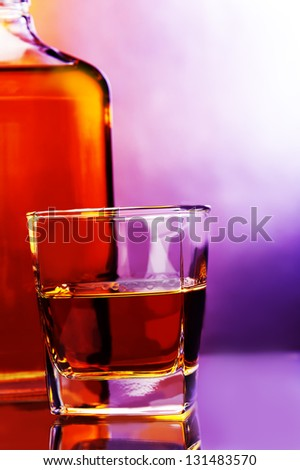 a glass of whiskey and bottle of whiskey against color background