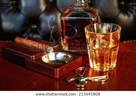 A glass of whiskey and cigar on a wooden table - stock photo
