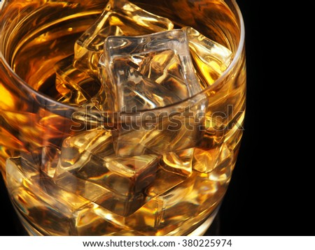 A glass of whiskey and ice on a black background. - stock photo