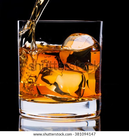 A glass of whiskey and ice on a black background