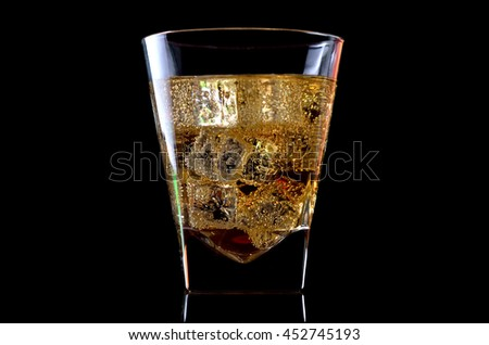 A glass of whiskey with ice isolated on a black background. Alcohol in a glass closeup.
