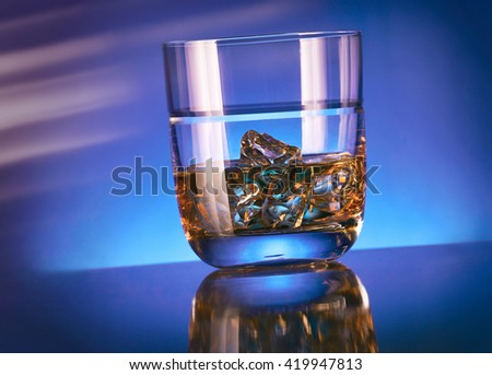 A glass of whisky with ice on a modern reflective bar top and blue background.