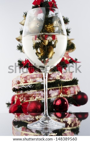 a glass of white wine and Christmas tree at background - stock photo