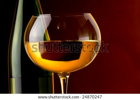 a glass of white wine and green bottle