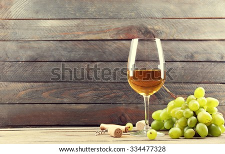 A glass of white wine and green grapes on wooden background