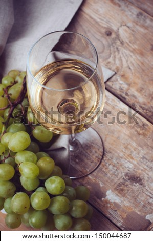 A glass of white wine, grapes, coarse linen cloth on a wooden board, closeup