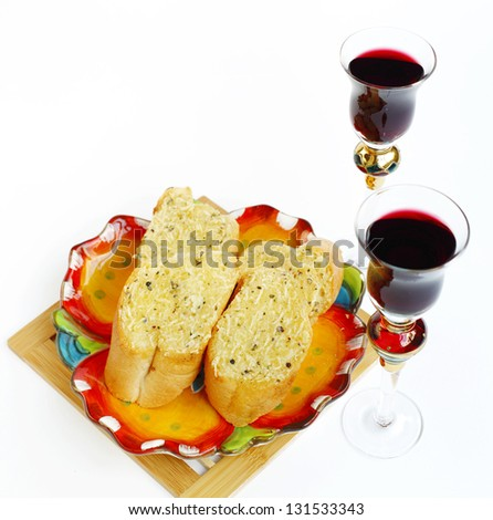 A glass of wine and garlic bread