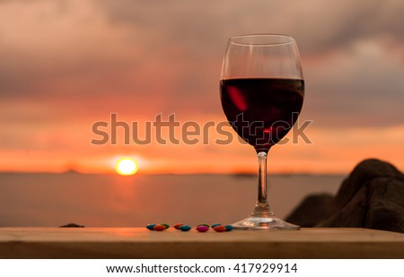 a glass of wine facing sunset. image mya contain soft focus due to shallow DOF. - stock photo