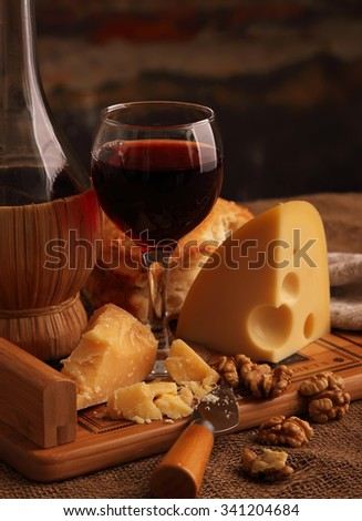 A glass of wine, hard, aged cheese and nuts.