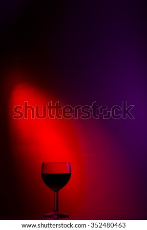 A glass of wine on a colored background, light, a colored dot studio lights