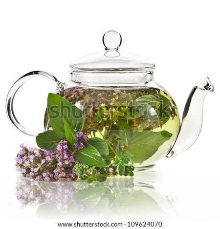 A glass tea pot with fragrant herbs isolated on a white background - stock photo