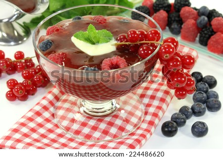 a glass with red fruit jelly, vanilla sauce and mint
