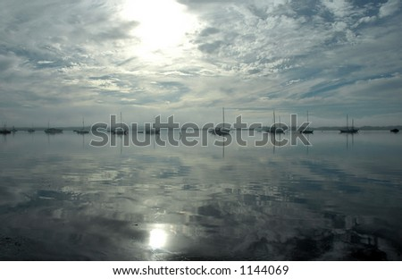 A glassy bay reflects the sun, sky and sailboats. - stock photo