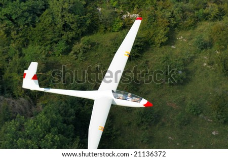 A glider Janus A flying over Alps forest at Challes les eaux France - stock photo