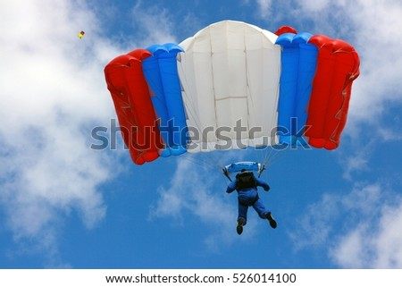 A gliding parachutist with a parachute color of Russian flag against blue sky