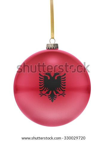A glossy christmas ball in the national colors of Albania hanging on a golden string isolated on a white background.(series) - stock photo