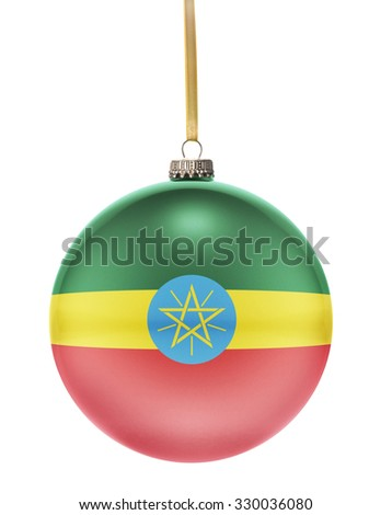 A glossy christmas ball in the national colors of Ethiopia hanging on a golden string isolated on a white background.(series) - stock photo