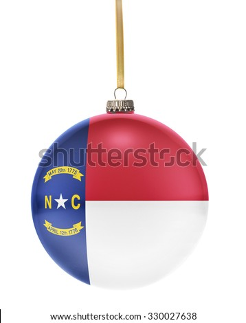 A glossy christmas ball in the national colors of North Carolina hanging on a golden string isolated on a white background.(series) - stock photo